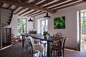 Long wooden table and Thonet chairs in rustic interior with paved floor