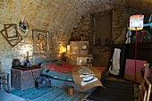 Artistically furnished bedroom under vaulted stone ceiling