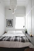 Doppelbett vor Fenster in schmalem Schlafzimmer mit schlichter Wand- und Deckenvertäfelung in Weiss