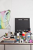 Paint pots, spray cans and drawing utensils on metal table in front of picture of bear and pegboard