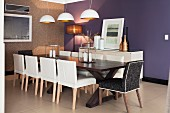 White leather chairs at long, dark-wood table below pendant lamps with white and gold lampshades; purple-painted accent wall in background