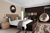 Elegant bedroom in shades of brown - ottoman at foot of double bed and hanging chair