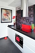 Kitchen counter with white base units, black worksurface and cylindrical, stainless steel extractor hood above cooker