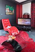 Couchtisch aus Glas vor Tagesliege mit rotem Lederbezug, im Hintergrund Fernseher auf Boden