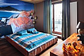 Double bed with striped bedspread against wall with poster mural of coastline and ocean