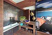Badewanne neben Waschtisch und Messing Hängeleuchten im Designerbad mit Mosaikfliesen