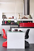 Red and black shell chairs at white table in open-plan designer kitchen