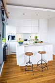 Open-plan kitchen with industrial-style bar stools at counter