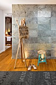 Bag hanging from wooden coat stand, stool and rug with pattern of lettering in front of wall covered in stone tiles