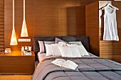 Elegant bed against wood-clad wall flanked by integrated bedside table and wardrobe