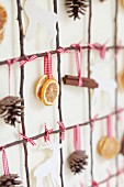 Grid of twigs decorated with pine cones, citrus slices, cinnamon sticks and stags