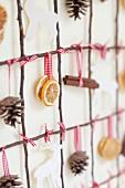 Gitter aus Zweigen dekoriert mit Zapfen, Zitrusscheiben, Zimtstangen & Elchen