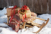 Two gift-wrapped presents and striped blanket on wooden sledge in snow