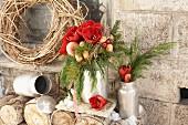Ein winterlicher Blumenstrauß mit Amaryllis, Nüssen, Äpfeln und Thuja-Zweigen in alten Milchkannen aus Blech