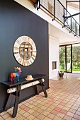 Colourful stag ornament on black table below round mirror on black wall in contemporary house with tiled and wooden floor
