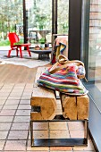 Striped fabric bag on rustic wooden bench with metal frame