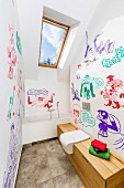 Modern attic bathroom with comic-style murals in various colours