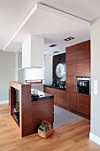 Open-plan designer kitchen with exotic wood fronts and black glossy worksurfaces