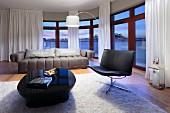 Eleganter Sitzbereich mit Ledersessel und Hochglanztisch vor geschwungener Fensterfront in der Abenddämmerung