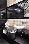 Washstand in designer bathroom with black glossy doors and back wall in subtle tartan