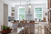View across dining set to free-standing island counter in country-house kitchen with white cabinets and lattice windows
