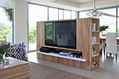 Free-standing wooden cabinet with integrated flatscreen TV used as partition in front of lounge area in open-plan interior with glass wall