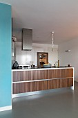 Island counter with wide wooden drawer elements in open-plan modern kitchen
