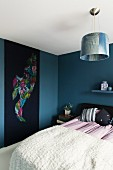 Bed with white cover and wall-hanging on blue-painted wall of modern bedroom