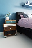 Bedside cabinet made from different drawers on castors next to bed against blue-painted wall