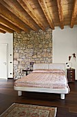 White modern bed with elegant cover in bedroom with wood-beamed ceiling and section of stone wall