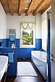 Long, modern bathroom with blue mosaic tiles and wood-beamed ceiling