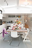 Cantilever chairs and Tripp Trapp child's chair around set dining table in open-plan houseboat interior