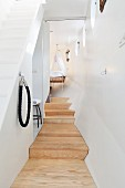 Wooden platform in narrow hallway and steps leading to cot with canopy in houseboat