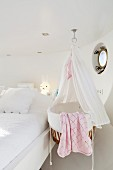 Cradle with canopy next to double bed in white bedroom of houseboat