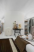 Bett mit Frühstückstablett, gegenüber Klapptisch mit Antiquitäten Sammlung, an Raumteiler unter Gewölbedecke
