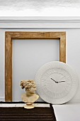 Antique bust of woman and clock sculpture in front of disused stone fire surround