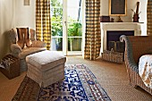 Footstool and armchair in corner of bedroom next to terrace doors with floor-length curtains