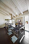 Modern kitchen counter with dark worksurface on metal frame and bar stools in rustic interior with white-painted wooden ceiling