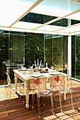 Ghost chairs around set table on wooden deck in conservatory below suspended, frosted-glass ceiling