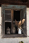 Enamel jug of dried flowers on windowsill of rustic wooden window