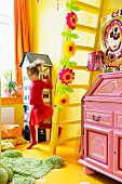 Pink bureau in child's bedroom with yellow wall, floor and ladder; girl running past