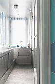 Shimmering silver surfaces in narrow bathroom