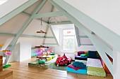 Bunt bezogene Matratzen und hängendes Klettergerüst unter Holzbalken in offener Dachkonstruktion