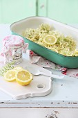 Elderflowers and lemons in green oven dish on white, vintage cabinet