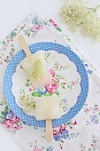 Home-made elderflower ice lollies on romantic floral plate on floral tablecloth