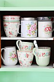 Romantic, vintage crockery with pattern of roses on pastel-green kitchen shelves