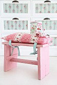 Romantic cushion with pattern of roses tied to pink, vintage stool and matching tin