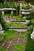 Garden steps leading to antique stone bench, planted urn & low columns