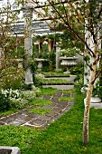 Antique columns lining path and steps leading to stone bench in seating area with planted urn