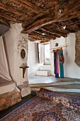 Oriental rug below concrete platform leading to staircase in rustic country house with wood-beamed ceiling